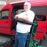 Author In Half-power Standing Chair Next To Ford Transit Equipped With Harmar AL690 Wheelchair Lift